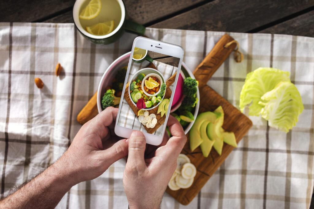 Un uomo scatta delle foto con uno smartphone ai piatti del suo ristorante