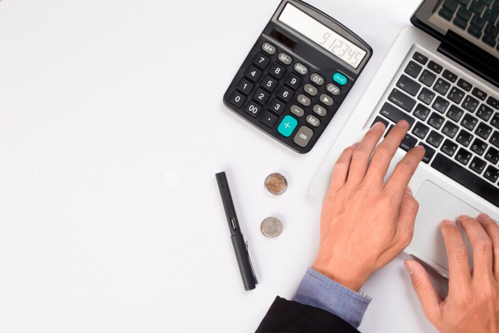 La mano di un uomo utilizza una calcolatrice posta su una scrivania con un computer
